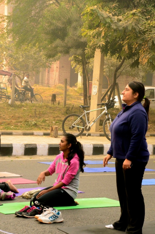 Yoga class starting up in the foreground, while passers by watch in the background. Watching other people is a great Indian pastime! And a wonderful one too...