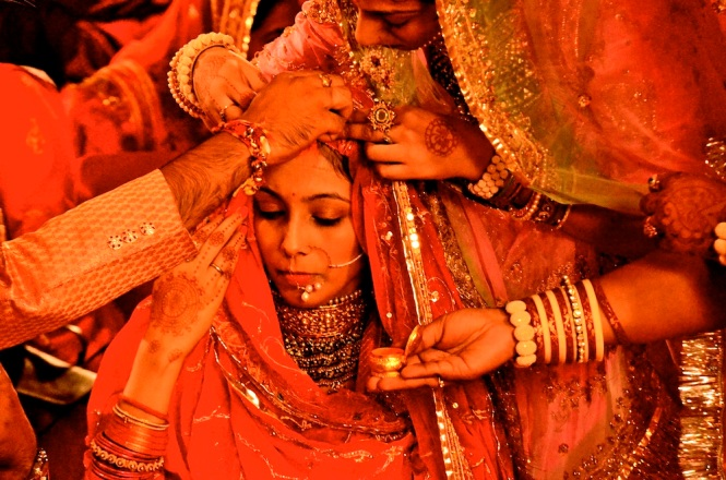 Maang mein sindoor. Red vermilion being filled into the parting on the bride's head by the groom. Her veil is lifted by the ladies and no one misses the poignancy of the moment. Love this capture!