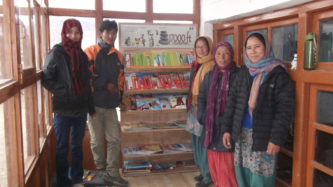 Pleased as punch! Teachers pose with their new library. They were as eager to read as the kids were!