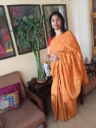Day 60 ‪#‎100sareepact‬ Draping this crisply starched cotton saree this morning made me realise that I'm finally living a childhood dream. Back in Lucknow in the late '80s, I shared a particular chore with our househelp's daughter and my close friend Gyanwati. It involved the mass starching and drying of Ma's sarees. We had a system to it. Long strips across the worthy of the front lawn in parallel rows, the sarees never touching with thin strips of the grass peeking out in long lines between them. And then lengthwise on the one half of the slightly deeper back lawn, the other half being our kitchen garden. And then running to gather them back before the sun dated bleached these beauties. A haze of colour. Laughing as we struggled with the stiff cotton lengths and pummelled them into submission, finally bundling them up for dhobi bhaiyya to iron. What a privileged childhood I had in that lovely campus far from the city! We would often wonder how mum feels draping these stiff but gorgeously vibrant sarees and I'm living that thought today. Gyanwati still lives there on the same campus, the smart mother of two very smart daughters. MA pass but still working as a domestic help, claiming its out of choice but we all know it's far more complicated than that!Yes, this is mum's saree. Handloom cotton with monochrome batik prints. It's mango yellow, nearly orange mirrors the sharp sunshine of September, heralding the oncoming winter and asking us to not be impatient in wishing it were cooler! Wearing it, paired with a maroon leheriya blouse, on a morning of nostalgia and contemplation, wanting it's hopeful hues to change my mood to one of resolve and enthusiasm instead.